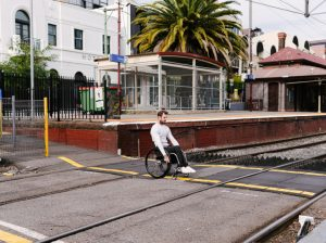 heath crossing the road at Prahran station in Melbourne while navigating the gaps in the footpath that train tracks create